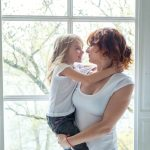 Woman holding child in front of window
