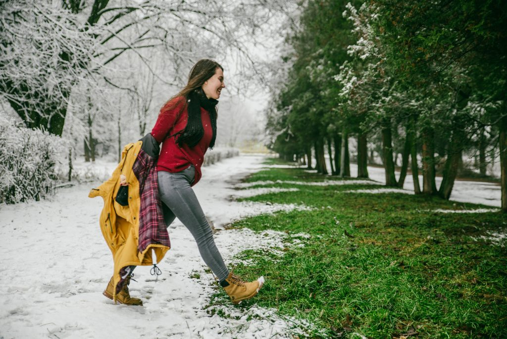 Girl walking out of snow into green trees