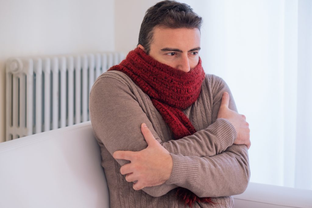 Man freezing and shivering in scarf